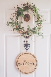 photo-of-a-white-door-with-a-hanging-wreath-and-welcome-1652394